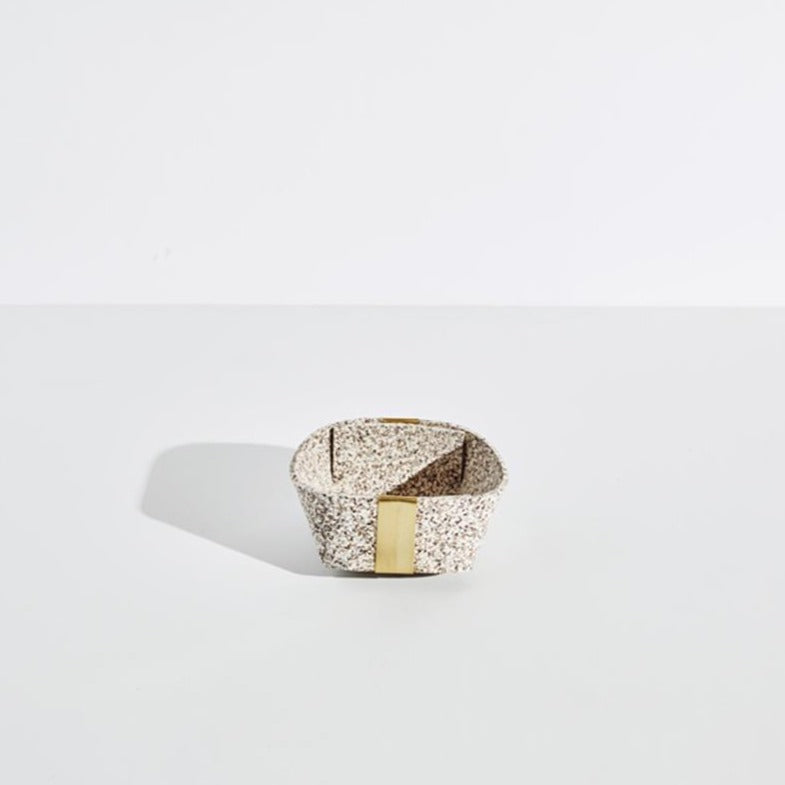 The small sand speckled basket with gold accents sits on a plain white background.
