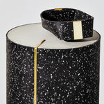 A black and white speckled tray sits atop a large, cylindrical stool made of the same design and material. There are gold accents on each. Striking.