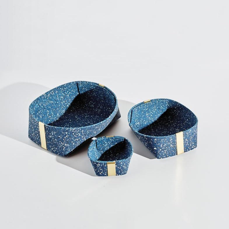 All 3 blue speckled nesting baskets sit separately so we can see the range of their sizes. Each has gold accents, and looks equally useful.