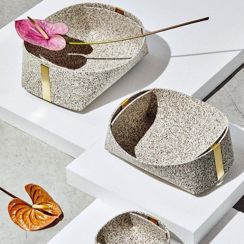 A set of sand colored recycled rubber and brass baskets, in ascending order of size.