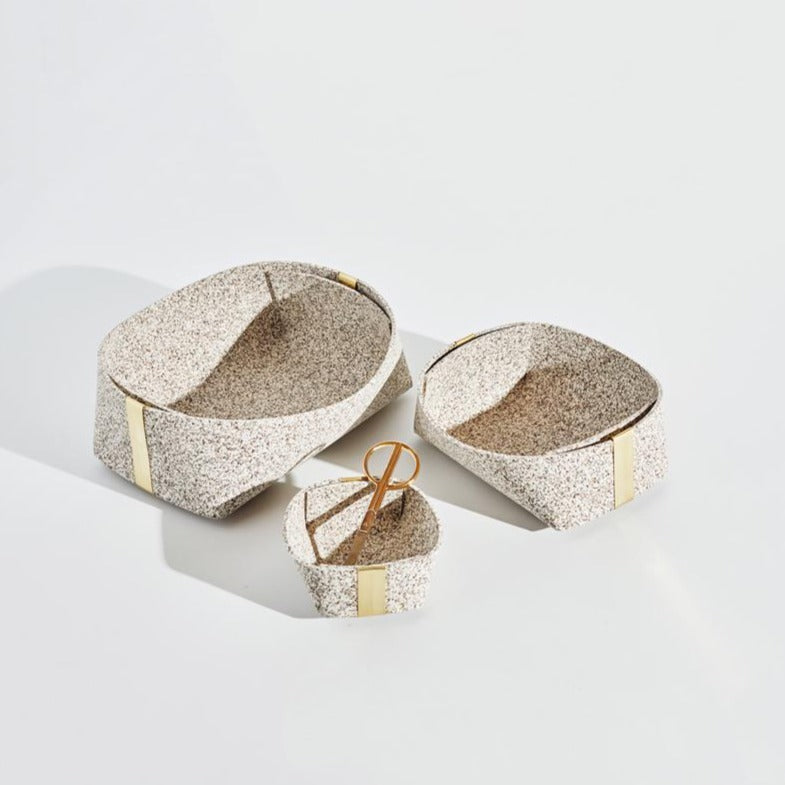 1 of each the small, medium and large sand speckled baskets sit in the middle of a plain white background. Each has gold tabs accenting their ends. A single pair of modern, gold scissors sits in the small sized basket.