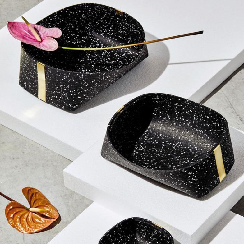 A set of three recycled rubber and brass baskets in ascending order of size. They are black and white speckled, and one even holds a pink flower. Calm.