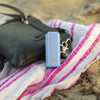 A purple Final. Straw carrying case is seen out in the wild! Lying on the beach, the case sits on top of a pink and white striped beach towel. The case then leans against a black cross body bag--truly the perfect companion for any adventure!