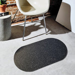 The speckled black recycled rubber door mat sits on a beautiful floor surrounded by other modern interior design accents.