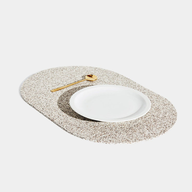 These durable placemats are made of the same sustainable recycled rubber that our favorite doormats and trivets are made of, so they're heat resistant, stain proof, and are a speckled beige, nude or sand terrazzo color. Each is shaped like a capsule! This is a side view.