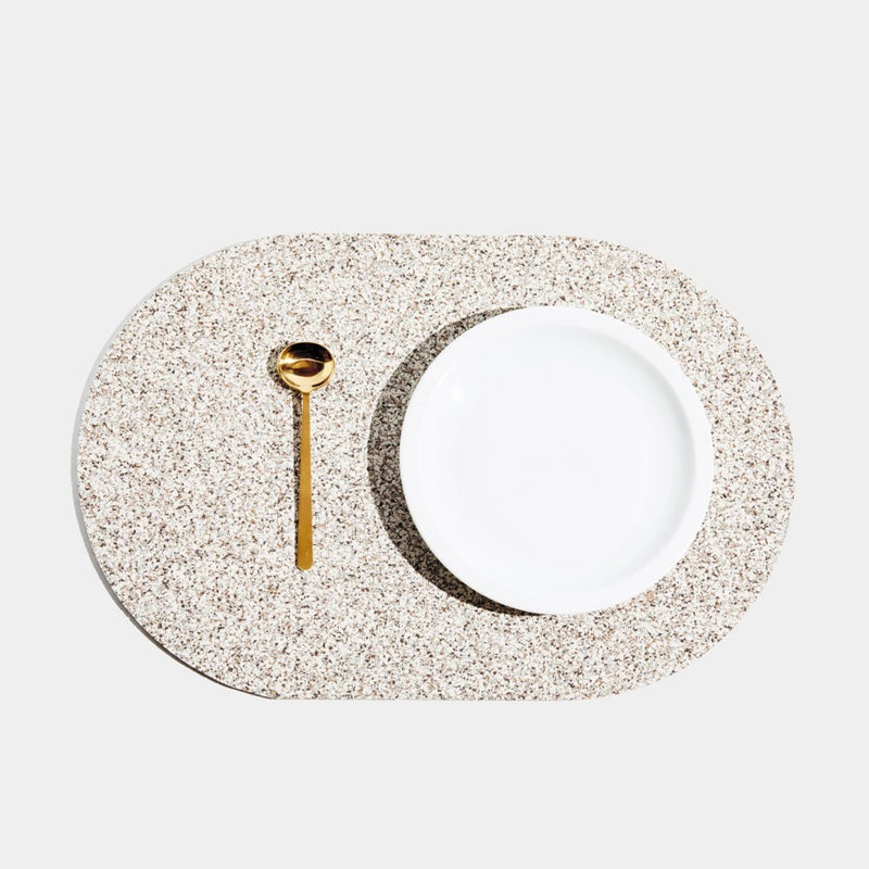 These durable placemats are made of the same sustainable recycled rubber that our favorite doormats and trivets are made of, so they're heat resistant, stain proof, and are a speckled beige or sand terrazzo color. Each is shaped like a capsule!