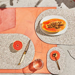These durable placemats are made of the same sustainable recycled rubber that our favorite doormats and trivets are made of, so they're heat resistant, stain proof, and are a speckled terrazzo color.  Here the color really pops because they're set against a bright background and accented with citrus and a giant papaya..