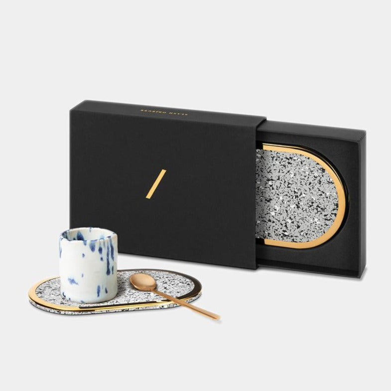 These grey brass edged coasters are made of recycled rubber. Here we can see them in action, including the beautiful giftable box they come in.