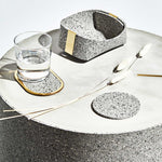 We're looking at a very modern, clean table setting. Atop we have one grey and black speckled coaster with a thick gold edge, a simple grey speckled basket with gold accents, and a grey and white speckled coaster. There are 3 pampas grass leaves are tossed across the table delicately.
