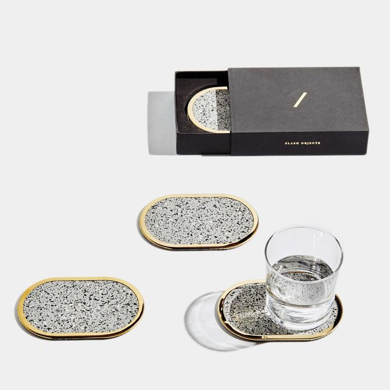 These brass edged coasters are made of recycled rubber. Here we can see them in action, including the beautiful giftable box they come in.