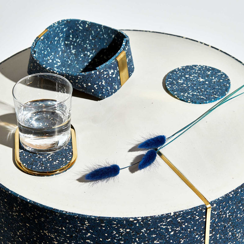 We're looking at a very modern, clean table setting. Atop we have one blue and white speckled coaster with a thick gold edge, a simple blue speckled basket with gold accents, and a blue and white speckled coaster. There are 3 blue pampas grass leaves are laid across the table delicately.