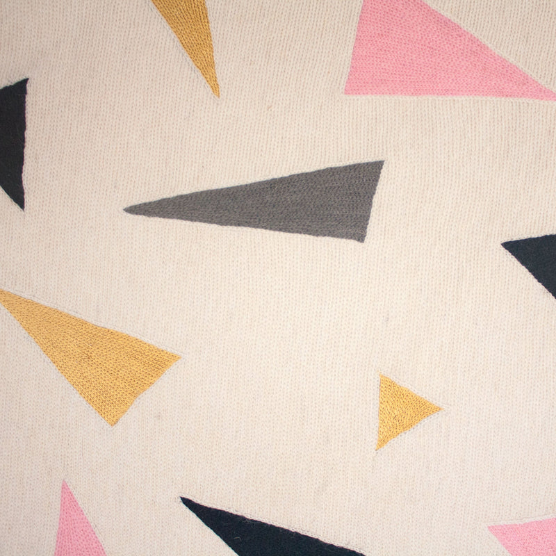 Close up of sustainable but bright carpet with pink, gold, grey and slate hand embroidery on natural fiber backdrop.