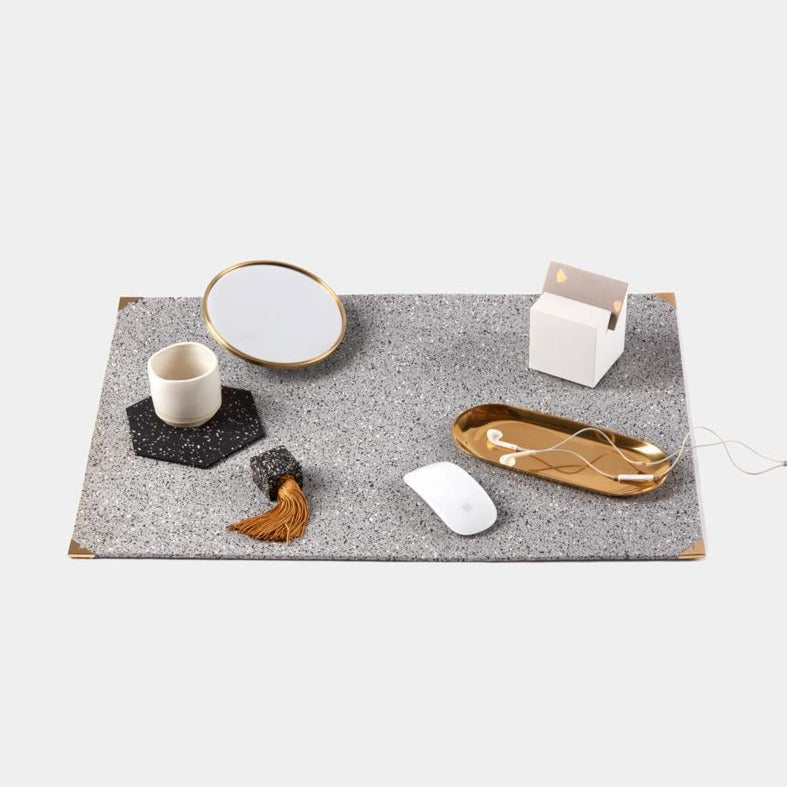 Speckled grey terrazzo deskmat with brass edges. It's made of a super sustainable recycled rubber material by hand in the US.
