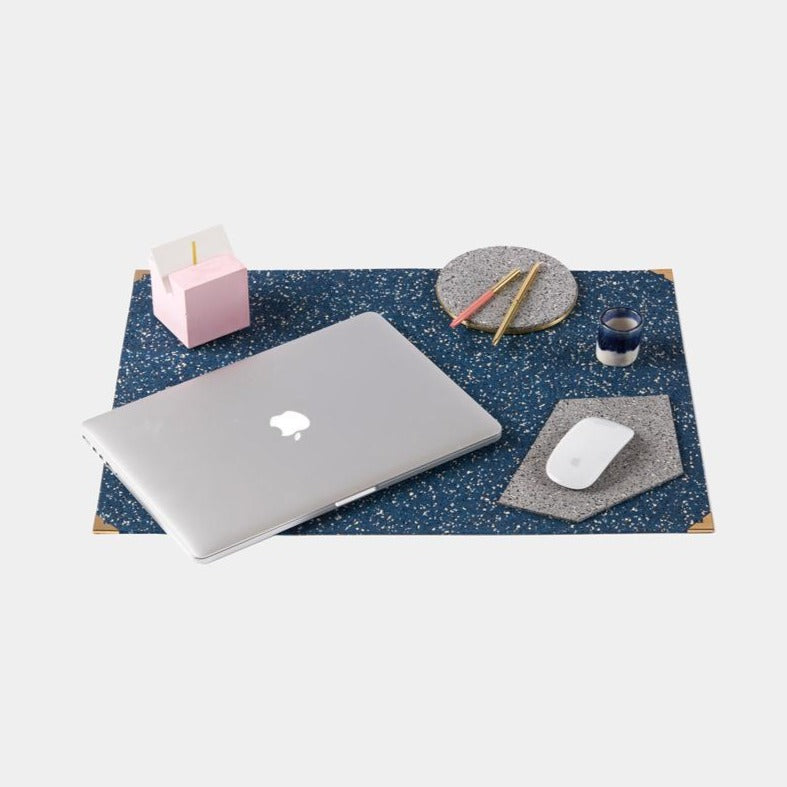 Speckled royal blue terrazzo deskmat with brass edges. It's made of a super sustainable recycled rubber material by hand in the US.