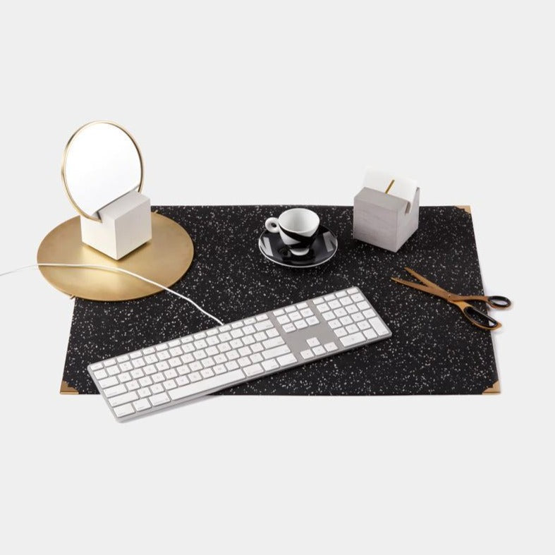Speckled black terrazzo deskmat with brass edges. It's made of a super sustainable recycled rubber material by hand in the US.