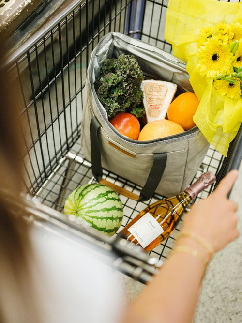 A sustainable grey cooler bag made from paper sits fully open, with the lid unzipped and folded over to the back, in a black grocery cart; it is full of veggies, fruit and cheese. In the basket is also a yellow bouquet of flowers, a bottle of sparkling rose, and a small melon. The bag is compact and totable at the grocery store while keeping cargo cool on your journey home or to a picnic.
