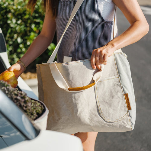 A women holds a grey cooler tote bag (made sustainably from paper!) on her left shoulder. She stands at an open hatchback car's trunk, filling her tote bag with groceries. She is holding a golden apple with her right hand, putting it inside the bag. Kale can be seen in another cooler bag in the car's trunk. She is keeping her groceries and food cold in the bag while she transports it into her home or to a park or beach picnic!