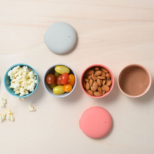 Four small snack containers made of sustainable bamboo sit in a horiztonal line on a very light wood table background. Lids for the containers are artfully arranged around the line of containers, along with one matching spoon. On the left, a blue bamboo snack pod is filled with popcorn, a smoke lightish grey is filled with tomatoes to its right, and second from right is a salmon pink bento box container, just like the rest, full of almonds. The last container, a soft blush, is full of pudding.