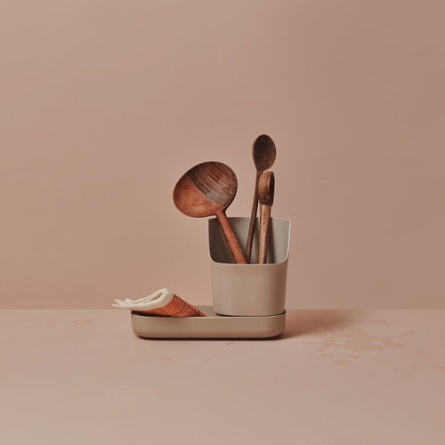 On a beautiful blush set background, the counter caddy sits. The bottom piece is flat and long, perfect to accommodate a biodegradable or sustainable sponge or bar of dish or hand soap. The taller part of the vessel is cup like in shape, with a rounded top that dips low in front for easy access. It's holding artful wooden spoons here.