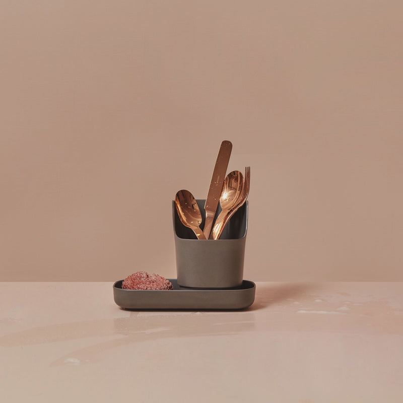This two piece countertop caddy is made of sustainable bamboo. This one is dark grey, on a blush background, and is holding a copper dish scrubber and copper spoons, a fork and a knife, all freshly washed.