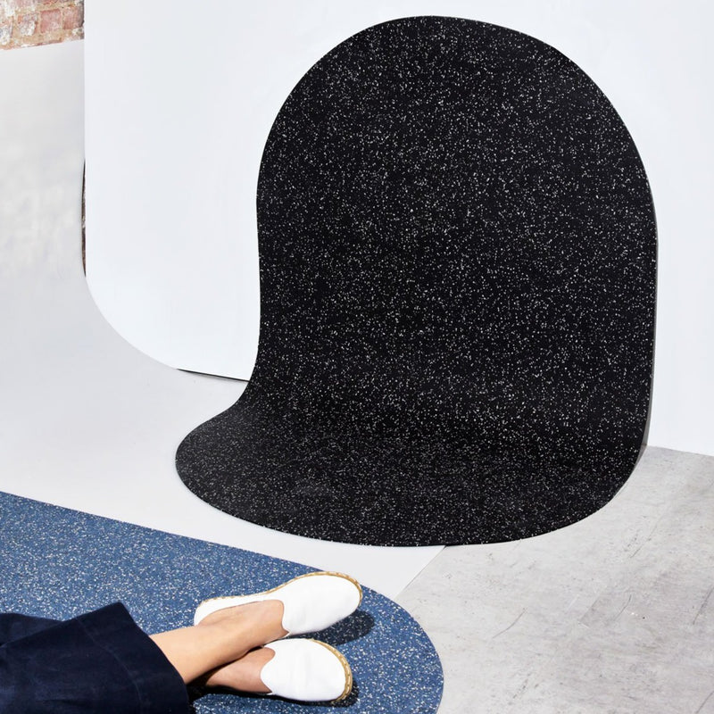 A large black floor mat is lying vertically-- that's different! It's actually made from a super sustainable LEED certified recycled rubber blend, is shaped like a capsule and not like a square or rectangle, and is super durable and heat resistant. It's a great floor or door mat for indoor or outdoor use and looks really sleek and speckled like a terrazzo print almost.