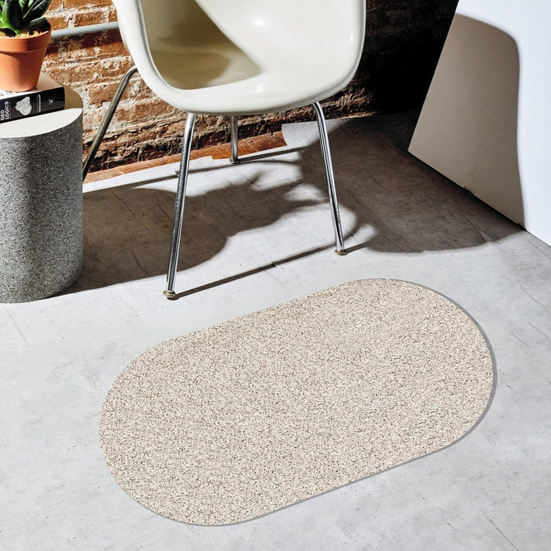 The speckled grey recycled rubber door mat sits on a beautiful floor surrounded by other modern interior design accents.