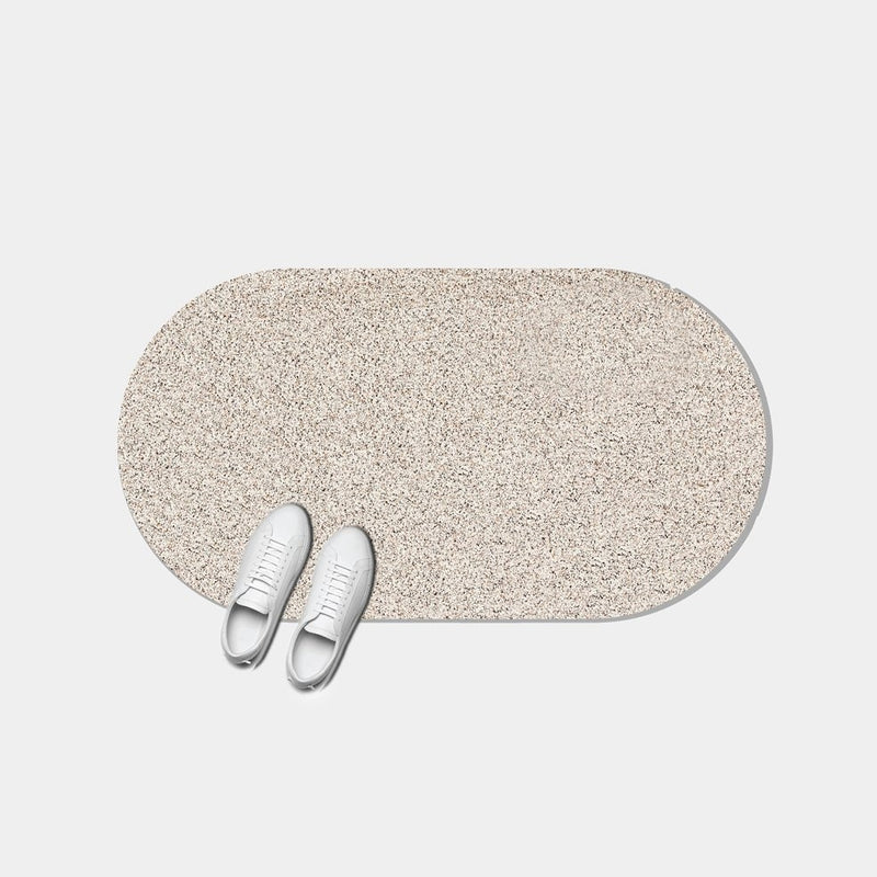 This sand colored capsule shaped door mat is stylish as can be and speckled because of its super sustainable and durable recycled rubber material. It's 20x36 and perfect for indoor and outdoor use.