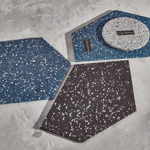 2 blue and white speckled, and 1 black and white speckled, abstract pentagon shaped mouse pads sit on a brightly lit concrete slab. On top of one blue and white mat sits a grey, black and white speckled trivet.