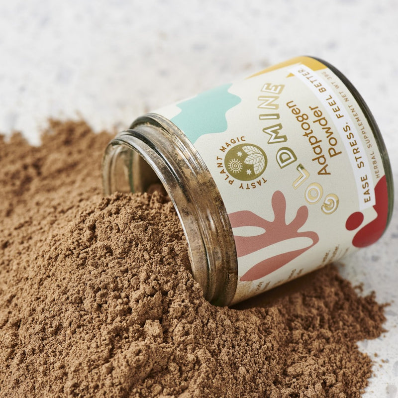 A lidless, glass mason jar with colorful labeling rests atop a bountiful pile of its own contents--golden brown, sustainable adaptogen powder.