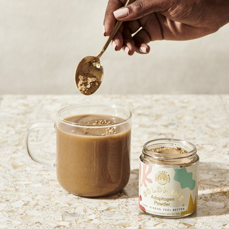 A double-walled glass mug sits in the foreground, filled with a tantalizing cocoa or coffee beverage. A manicured, black woman's hand hovers above wielding a golden spoon, scooping a delicious dollop of sustainable, golden brown adaptogen powder onto the beverage. An opened glass mason jar filled with Goldmine adaptogen powder sits neatly next to the beverage, with ample contents to spare.