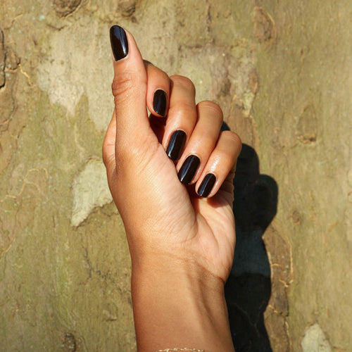 A womans hand up against an artistic wall, shows off the darkest shade of nail polish.