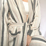 Here, we see the Hamman Turkish robe on a model, wearing a bright White bra with the robe tied tightly around their waist. The robe drapes the model's body and highlights the robe's intricate, foot-woven design and sustainable, vegetable-based dye. With thick grey stripes and thin rainbow stripes, the robe brightens an otherwise neutral image.