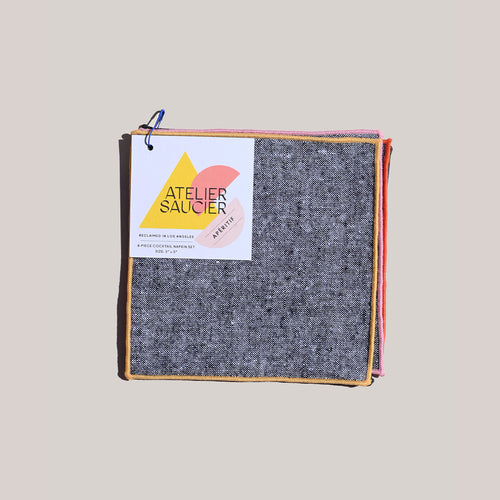 A flat lay image of a single set of 4 charcoal chambray with colorfully embroidered seamed cocktail napkins sits in the center. Pinned to the top napkin's left corner is a white, recyclable label donning Atelier Saucier's citrus colored, geometric design label.