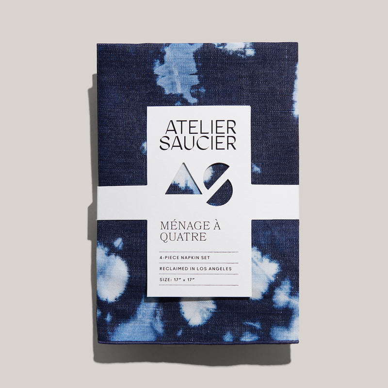 An upcycled, locally made, set of 4 tie-dye, denim, linen napkins are neatly folded in center frame. They're held together in place by a white recyclable sleeve. Each is embroidered with navy seam.