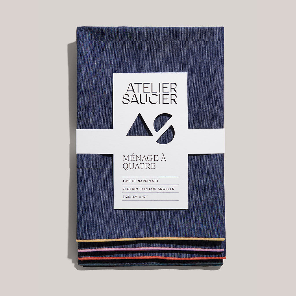 An upcycled, locally made, set of 4 denim and twill napkins are neatly folded in center frame. They're held together in place by a white recyclable sleeve. Each is embroidered with a different color – yellow, pink, red and navy.