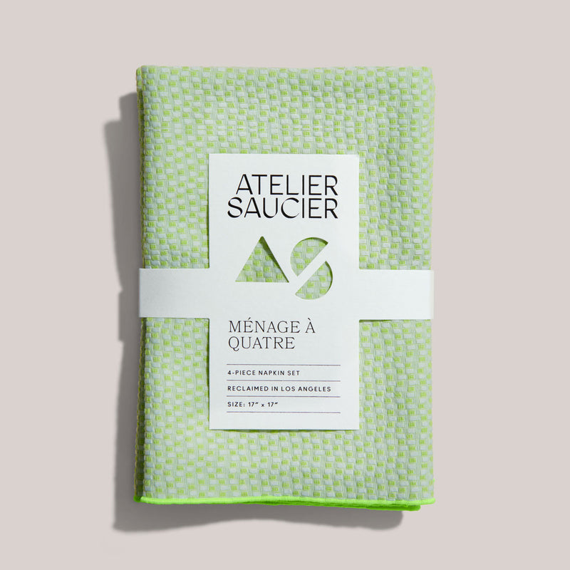A bright, loosely checkered, pastel green and light blue set of 4 piece electric weave napkins are neatly folded, tucked in with a recyclable white sleeve label. The seams are light green, these are very splashy and fun.
