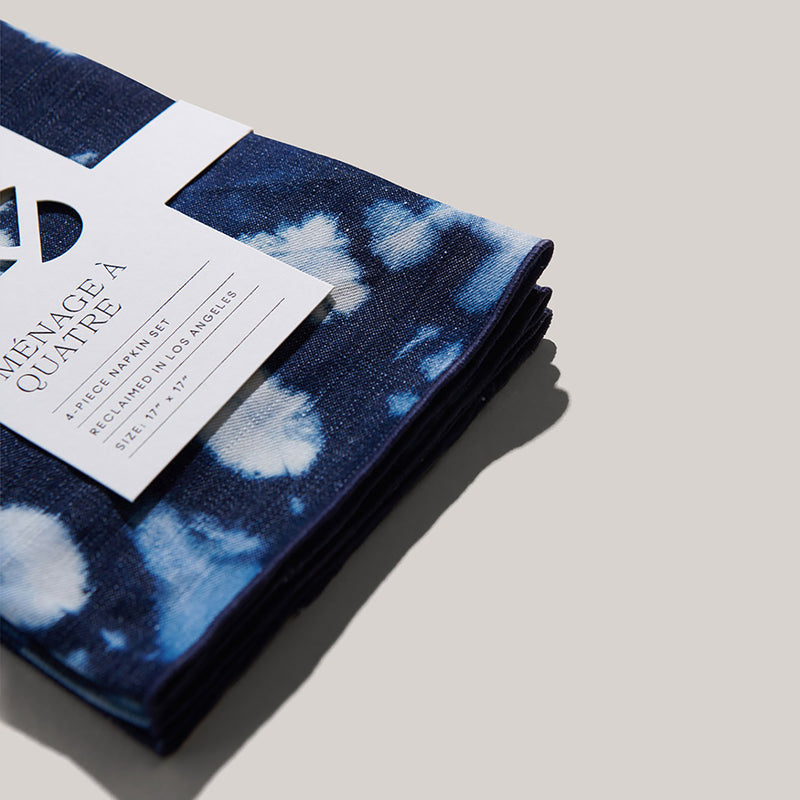 A close-up view of the tie-dye linen denim napkin set's embroidered navy seams. These are tucked neatly in place with the recyclable, white, paper sleeve label.