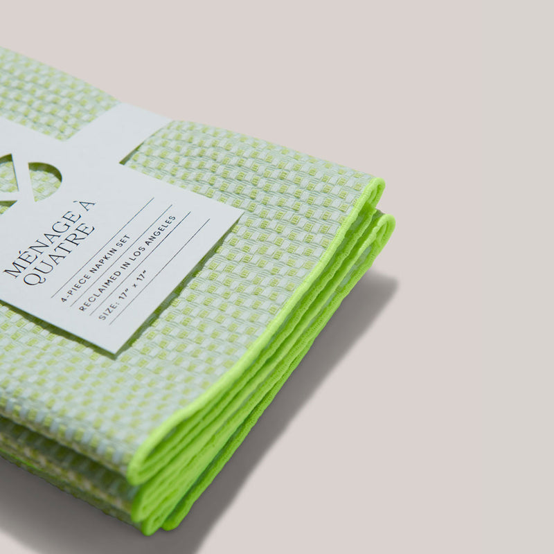 These electric weave napkins are sturdy and durable--we can see exactly how thick they are from this side view of the set of 4 electric weave bright and lime green tucked neatly in its white, recyclable sleeve label.
