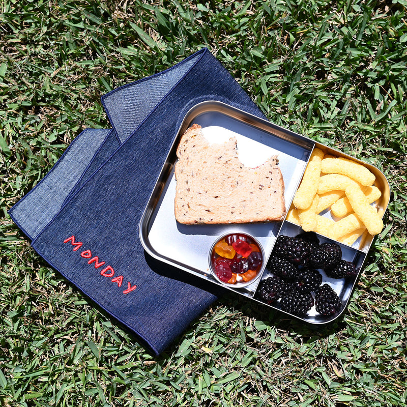 We're at a picnic in the grass. Looking down, we see a bento box filled with a multigrain sandwich, blackberries, organic cheese puffs, and some natural gummies--cushioned by an upcycled denim chambray napkin, embroidered in red with the word MONDAY.