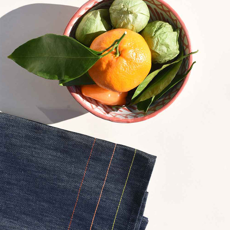 A handmade, hand-painted, white and orange ceramic bowl is filled with green tomatillos, red tomatos, an orange and a few orange leaves. A jewel demin upcycled tea towel with colorful seams is neatly folded nearby.