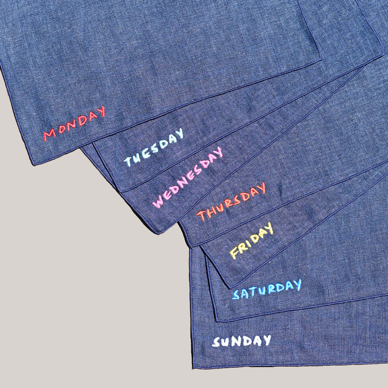 We're at a wooden picnic table. There are 7 upcycled, denim chambray, dark blue napkins casually spread out so that we can see which day of the week is embroidered in different colors at the bottom left corner of each.