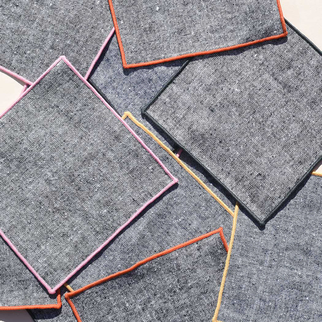 About 10 charcoal chambray cocktail napkins are splayed about a simple off white background. Each is embroidered in a different color--yellow, orange, pink and black.