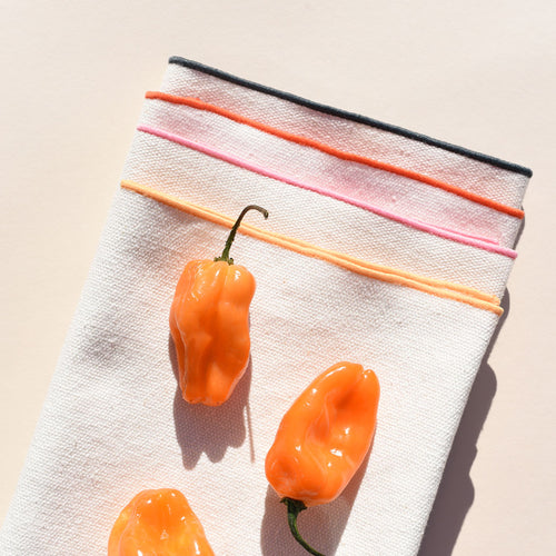 A set of 4 white burlap napkins are folded neatly on top of one another, splayed out so we can see the different colored seam of each (peach, pink, red, teal). On top sits 3 plump, bright, orange peppers.