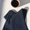 We're looking down at your first cup of coffee for the day--on a plain white countertop, we see a white ceramic, handmade mug holding a piping hot cup of coffee. Two jewel denim tea towels with colorful simple seams are folded casually nearby, a staple in this household.