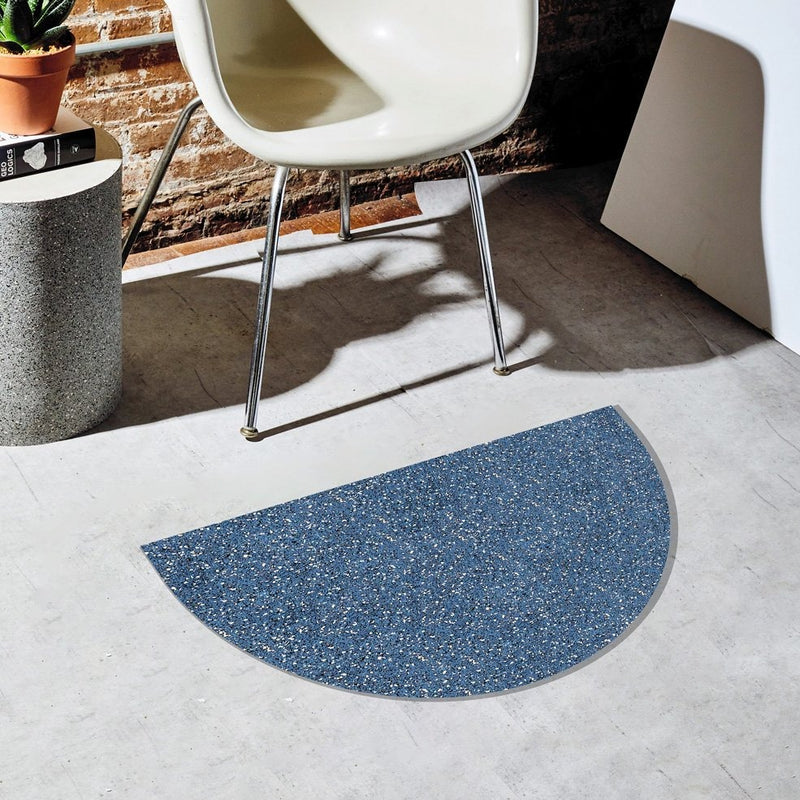 Half moon or semi circle shaped floor mat that's made of a super sustainable recycled rubber. It's sitting on a concrete floor next to other chic home accents.