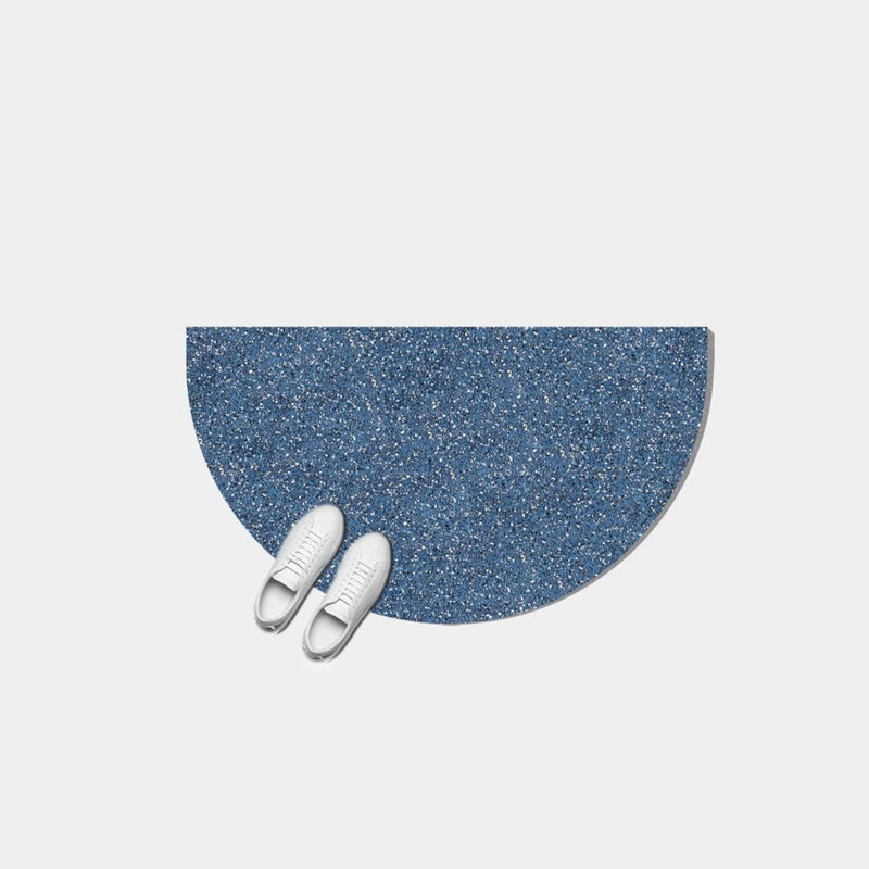 Half moon or semi circle shaped floor mat that's made of a super sustainable recycled rubber that has a terrazzo speckled effect and is a royal blue color.