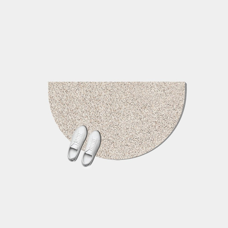 Half moon or semi circle shaped floor mat that's made of a super sustainable recycled rubber that has a terrazzo speckled effect and is a light beige.