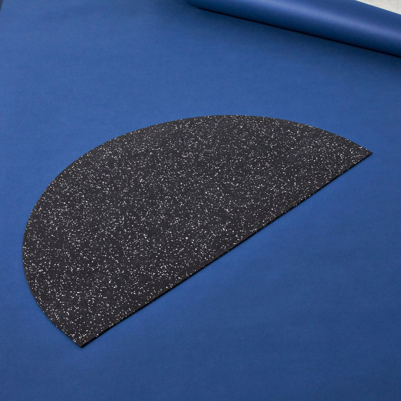 Half moon or semi circle shaped floor mat that's made of a super sustainable recycled rubber that has a terrazzo speckled effect and is a light beige. The mat is on a blue cobalt background.
