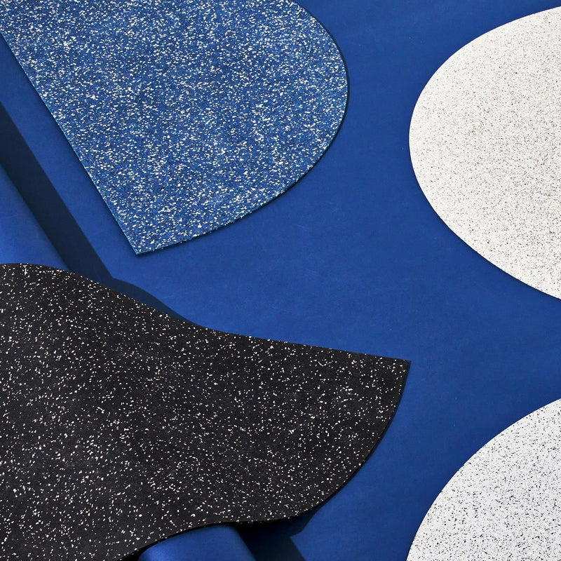 Half moon or semi circle shaped floor mat that's made of a super sustainable recycled rubber that has a terrazzo speckled effect and is a light beige. The mat is on a blue cobalt background and is next to a square shaped mat so you can compare and contrast sizing and the thickness of the durable, indoor/outdoor recycled rubber material.