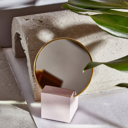 We're peering between some leaves into an opening—what's that? Oh, just a flawless blue vanity mirror with brass edge and rubber backing. It's sitting in its limited edition pink base. A mirror in the wild, who would've guessed.